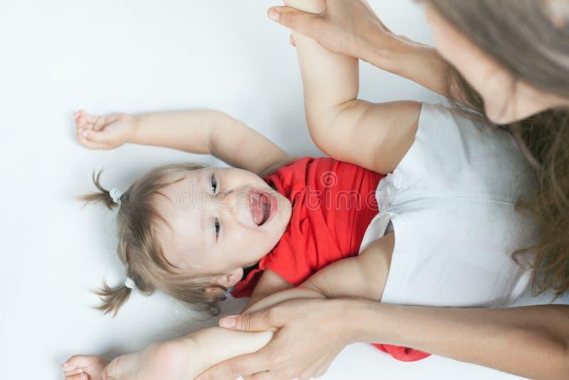 Roligt behandla som ett barn flickan som ligger nära lycklig moder på vit säng royaltyfri fotografi