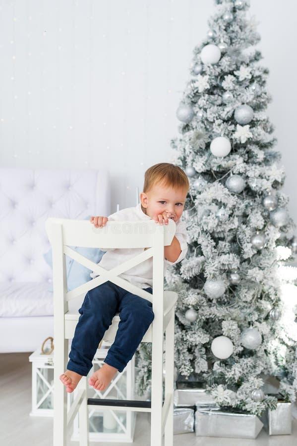 Roligt behandla som ett barn pojken som sitter i vit stol på julgranbakgrund royaltyfria bilder