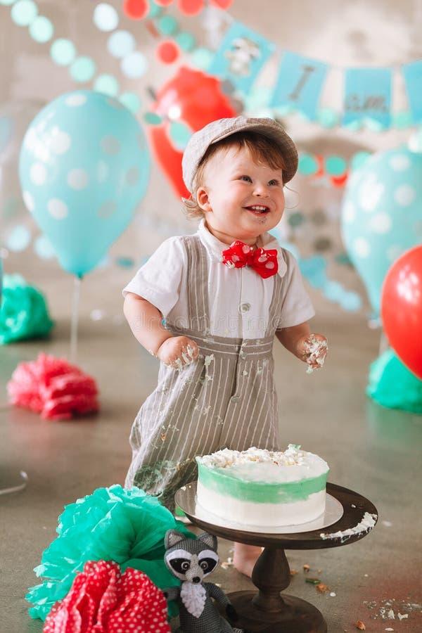 Roligt behandla som ett barn pojken som skrattar i hans första dundersuccé för födelsedagkakan Smutsiga smutsiga händer royaltyfri bild