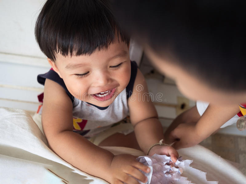 Roligt behandla som ett barn tycker om att spela ett styckpapper tillsammans arkivbild