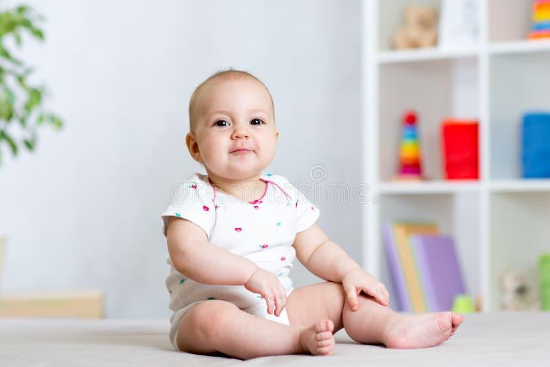 Roligt behandla som ett barn ungeflickasammanträde på golv i barnrum arkivbild