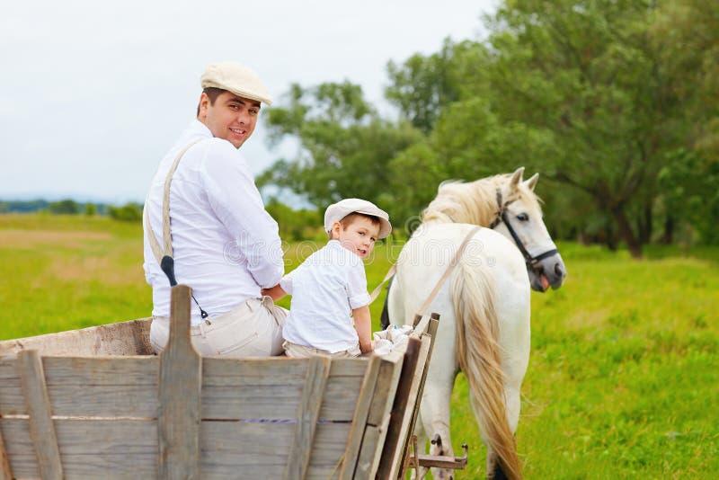 Roligt foto av den bondefamiljen och hästen som tillbaka ser royaltyfria foton