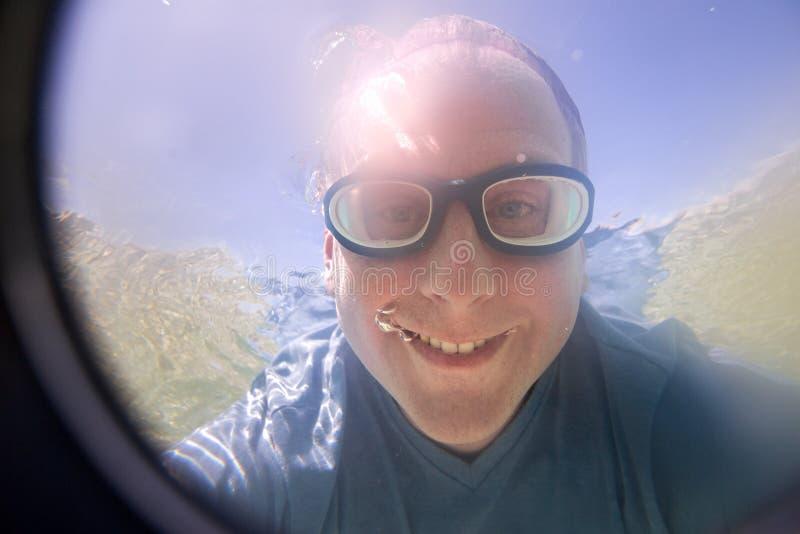 Roligt foto under vatten av den unga mannen royaltyfri bild