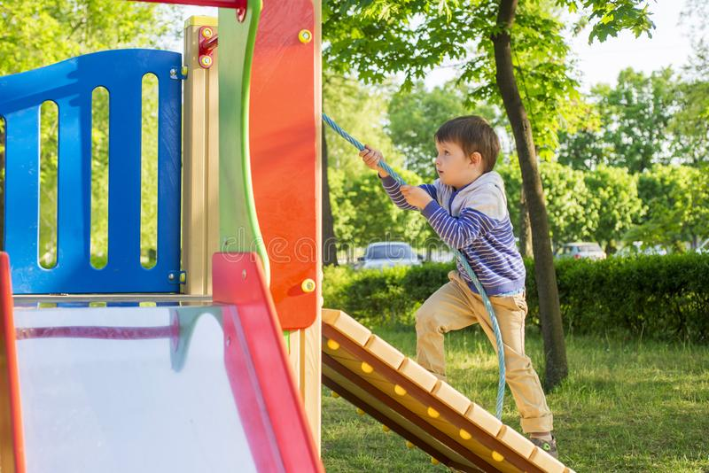 Roligt gulligt lyckligt behandla som ett barn att spela på lekplatsen Sinnesrörelsen av lycka, gyckel, glädje Aktiv pys som spela royaltyfria bilder