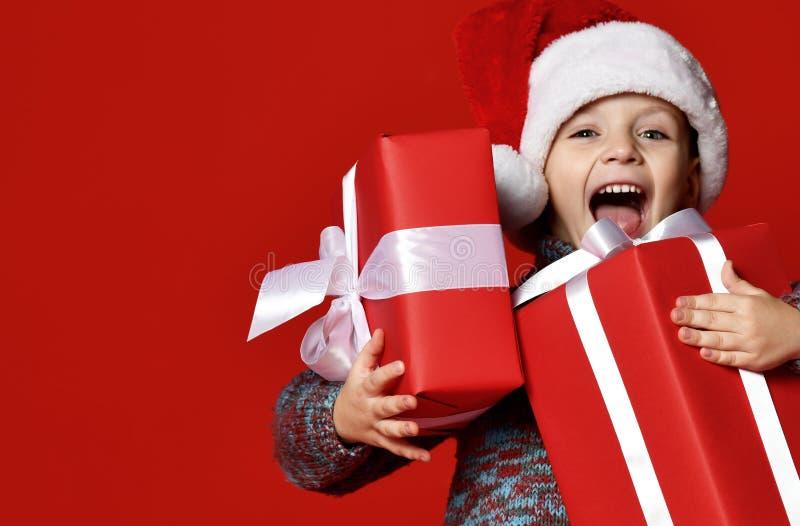 Roligt le barn i gåva för jul för röd hatt för jultomten hållande i hand royaltyfria bilder