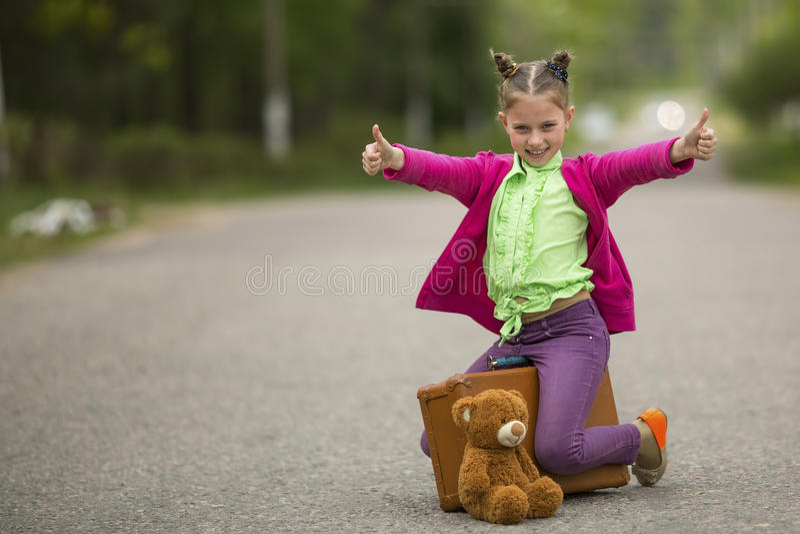 Roligt liten flickasammanträde på vägen med en resväska och en nallebjörn Lyckligt fotografering för bildbyråer