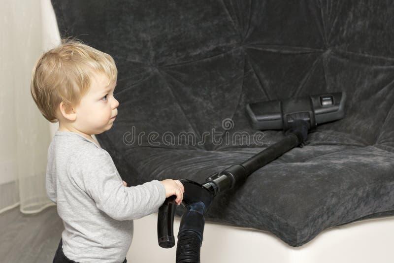 Roligt litet barn som upp gör ren soffan med dammsugare royaltyfria bilder