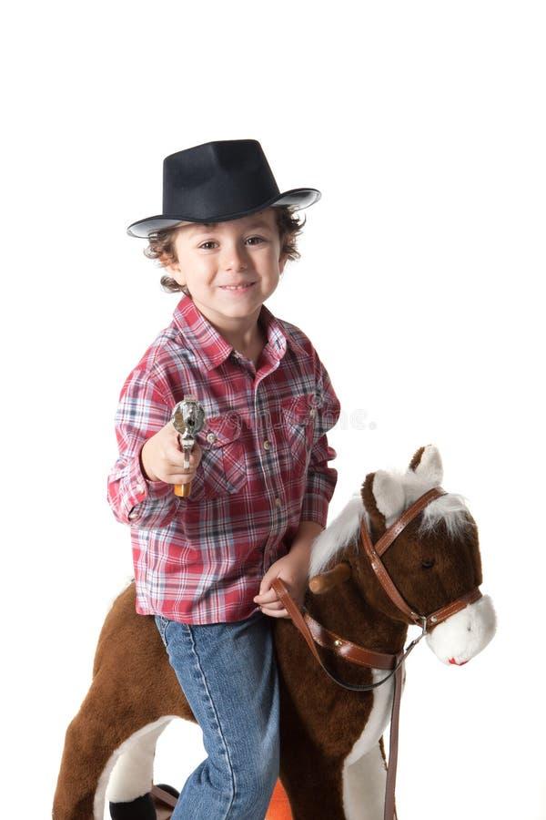 Roligt litet cawboy med den röda plädskjortan som rider en lekhäst royaltyfri bild