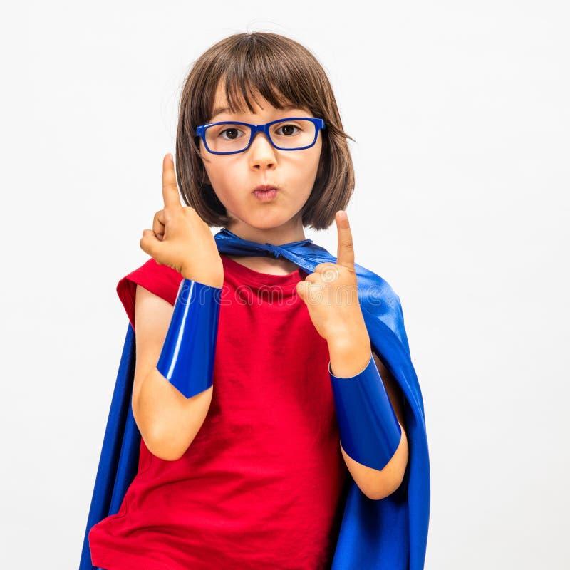 Roligt superherobarn som lyfter hennes begåvade fingrar för kritisk mindset royaltyfri fotografi