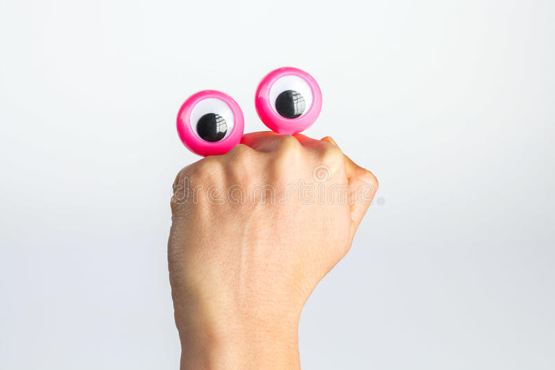 Roligt teckenvarelsenederlag bak den kvinnliga handen med googly e arkivfoto