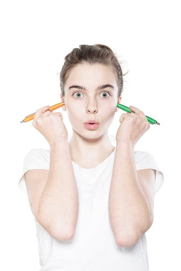 Roligt tonåringflickainnehav till pennor i hennes öron arkivfoton