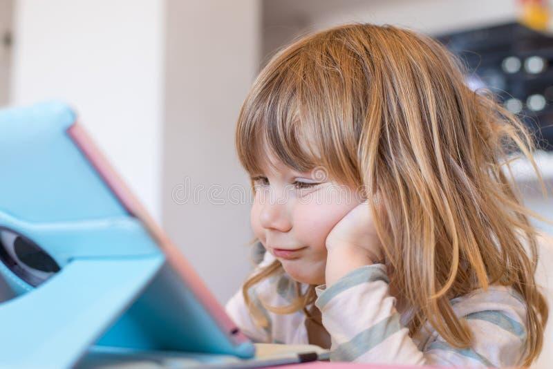 Roligt uttryck av det lilla barnet som håller ögonen på den digitala minnestavlan arkivfoto