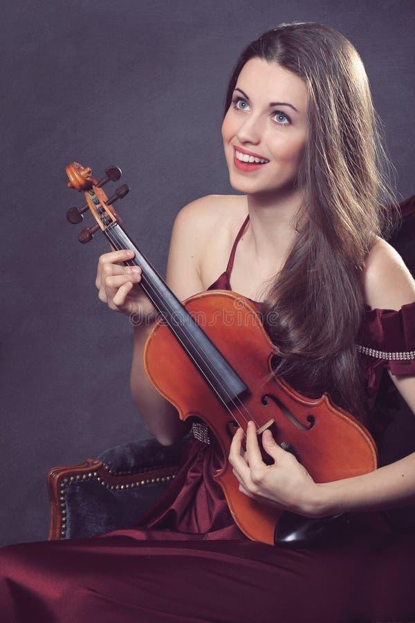 Rolig flicka som leker med en fiol royaltyfri bild