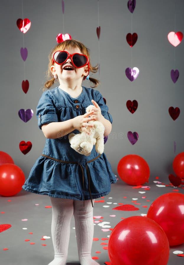 roligt vitt Caucasian liten flickalitet barn i studio med röda ballonghjärtor på grå bakgrund som bär roliga exponeringsglas royaltyfria foton