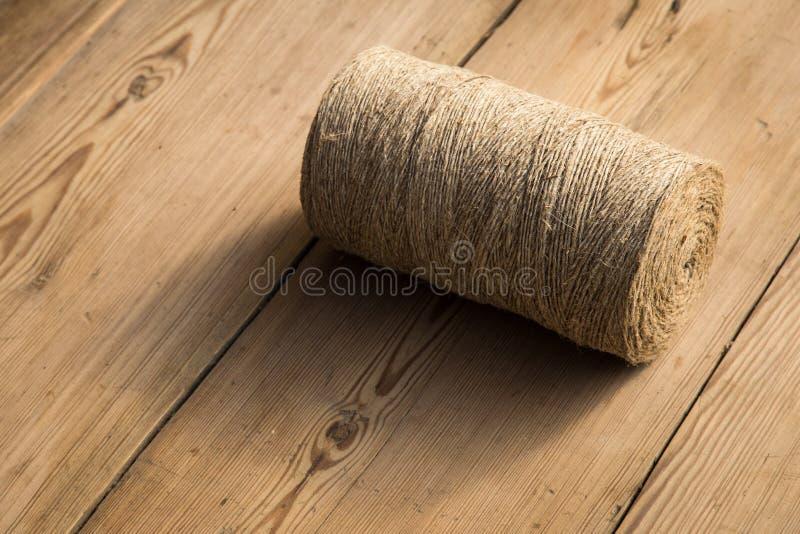 Rolka dratwa na drewnianym tle Selelective ostrość Zakończenie Uwalnia przestrzeń dla teksta zdjęcia royalty free