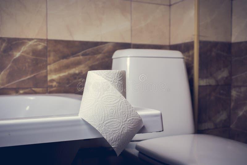 Rolka papier toaletowy na tle toaleta Na krawędzi skąpania Płytki i toaleta w tle zamazują zdjęcia stock
