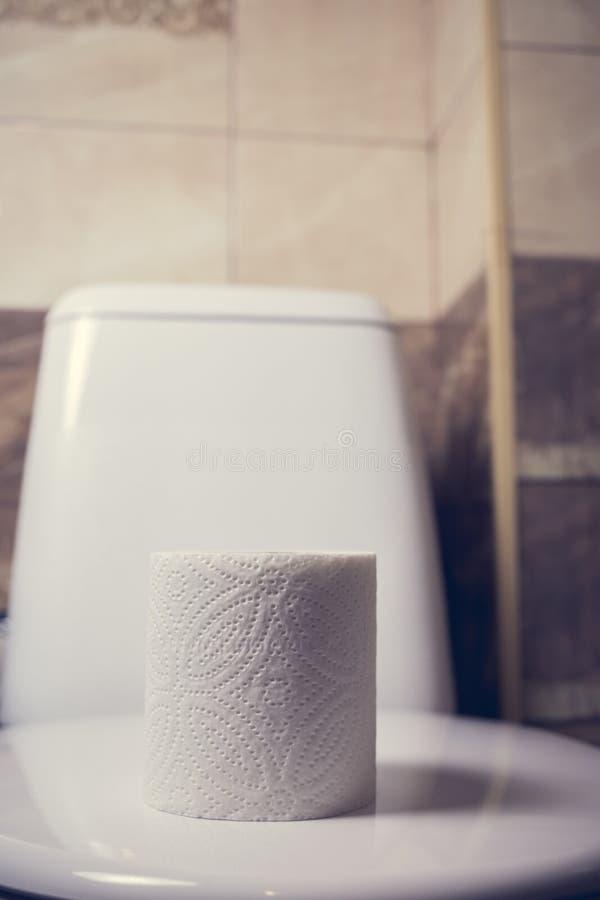 Rolka papier toaletowy na tle toaleta Na krawędzi skąpania Płytki i toaleta w tle zamazują fotografia stock