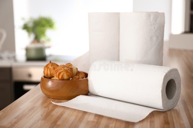 Rolki papierowi ręczniki z smakowitym ciastem na kuchennym stole zdjęcia royalty free