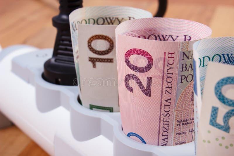 Rolki połysk waluty pieniądze w elektrycznej władzy pasku z związaną prymką, koszty energii fotografia stock