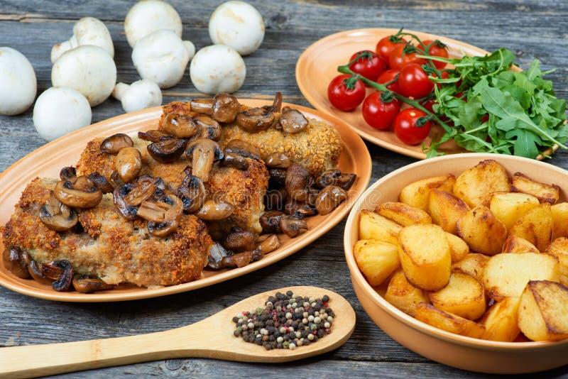 Rollè di carne di maiale con i funghi e le patate arrostiti immagini stock