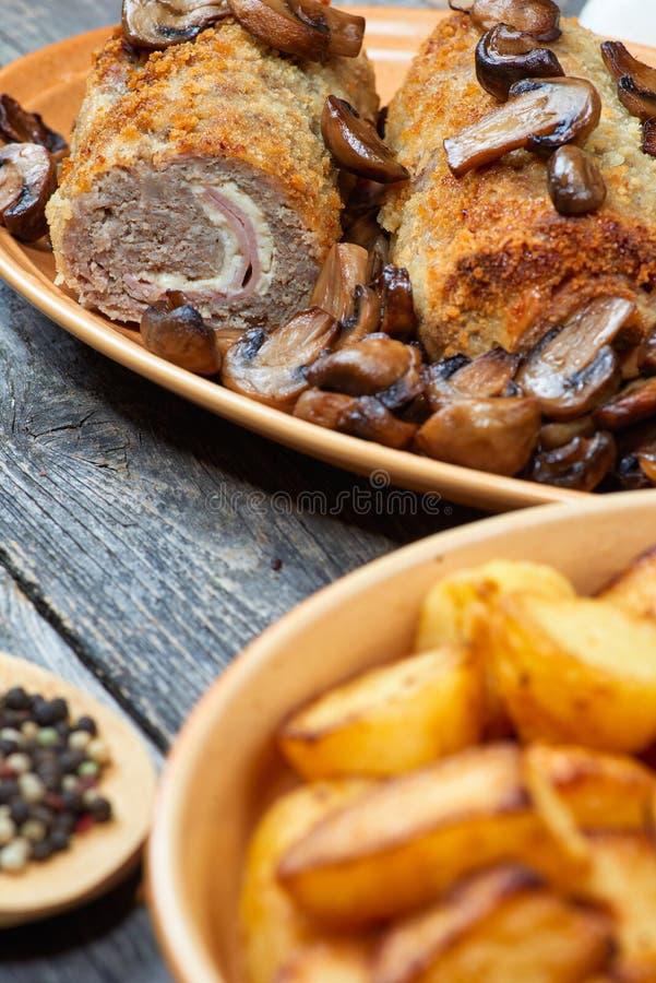 Rollè di carne di maiale con i funghi e le patate arrostiti fotografia stock