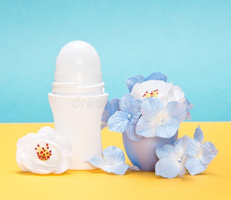 Roll-on antidiaforetico del deodorante del corpo con i fiori nel cappuccio immagini stock