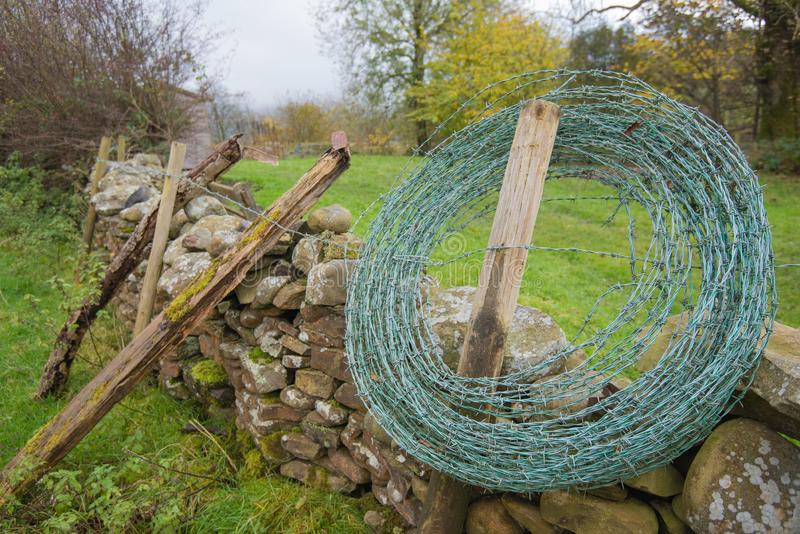 Roll of barbed wire ready to be added to an old dry stone wall stock images
