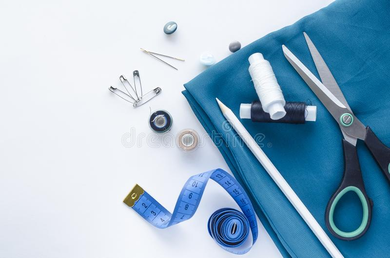 Roll of blue satin fabric, tape measure, scissors, needles. Fashion, Design studio for tailoring, atelier concept. stock images