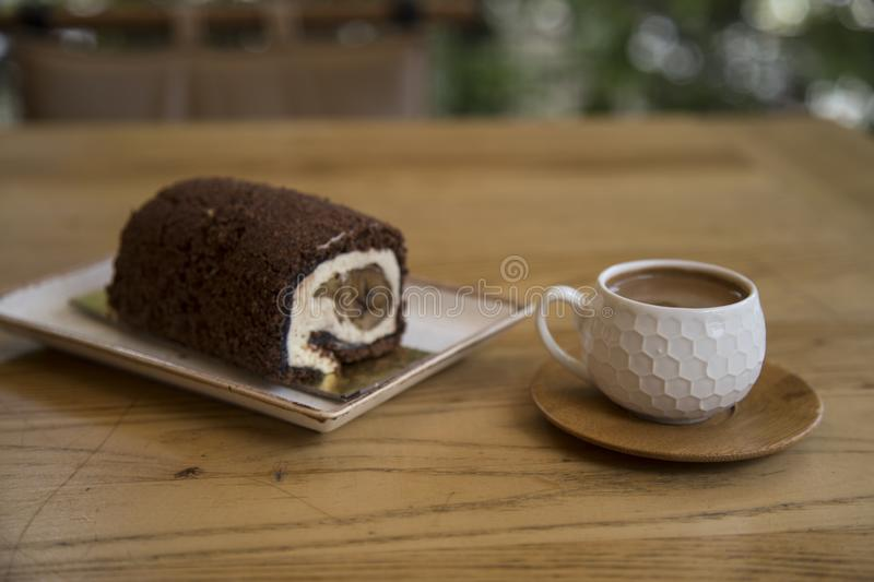 The roll cake and Turkish coffee service concept in the cafe . The roll cake and Turkish coffee service concept on the wooden background in the cafe stock images
