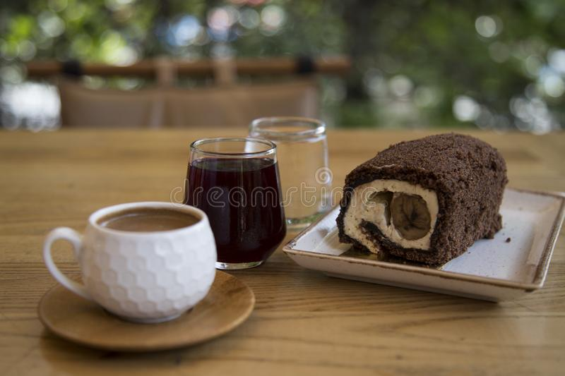 The roll cake and Turkish coffee service concept in the cafe . The roll cake and Turkish coffee service concept on the wooden background in the cafe stock photo