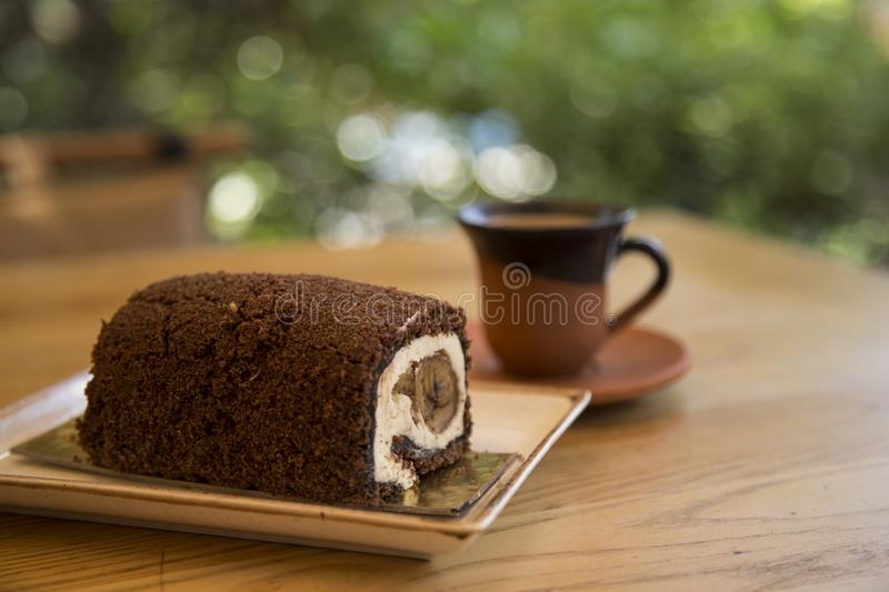 The roll cake and Turkish coffee service concept in the cafe . The roll cake and Turkish coffee service concept on the wooden background in the cafe stock photos