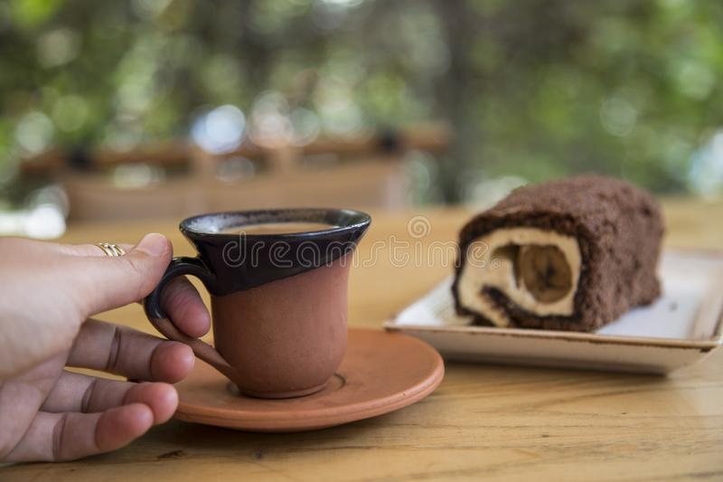 The roll cake and Turkish coffee service concept in the cafe . The roll cake and Turkish coffee service concept on the wooden background in the cafe stock photography