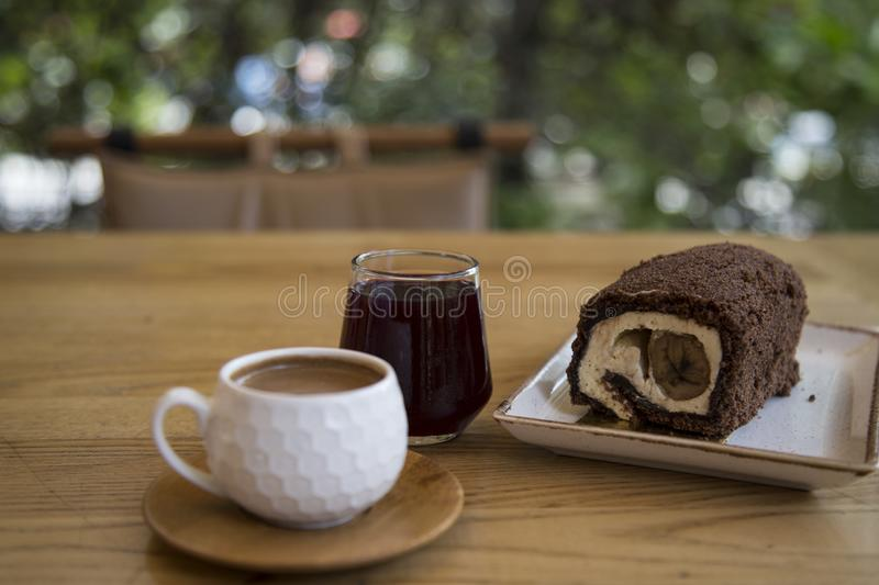 The roll cake and Turkish coffee service concept in the cafe . The roll cake and Turkish coffee service concept on the wooden background in the cafe royalty free stock photos
