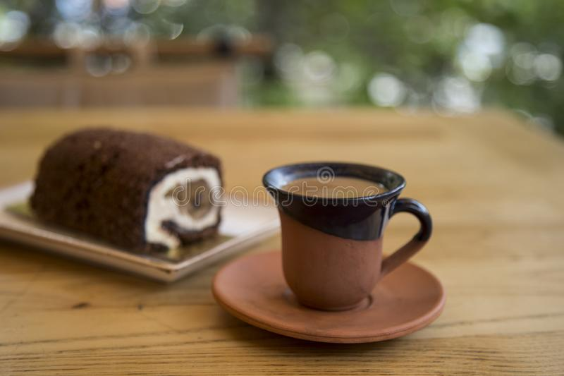 The roll cake and Turkish coffee service concept in the cafe . The roll cake and Turkish coffee service concept on the wooden background in the cafe royalty free stock images