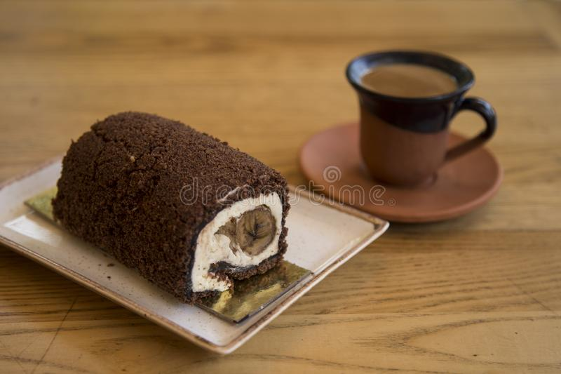 The roll cake and Turkish coffee service concept in the cafe . The roll cake and Turkish coffee service concept on the wooden background in the cafe royalty free stock image