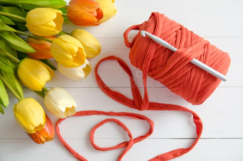 Roll of cotton yarn and a crochet hook with a bouquet of orange and yellow tulips on white wooden background. stock image
