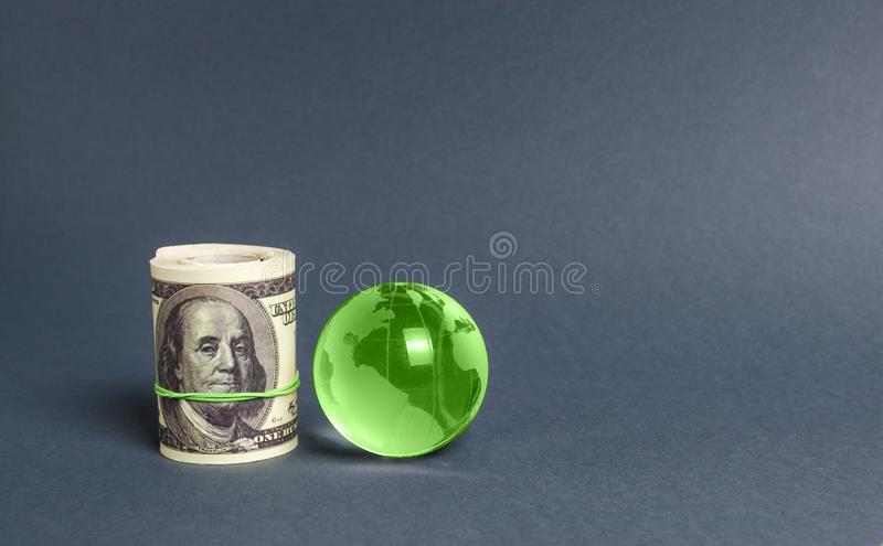 Roll of dollars and green planet earth globe. International money transfers, attraction of investments. Global financial system stock images