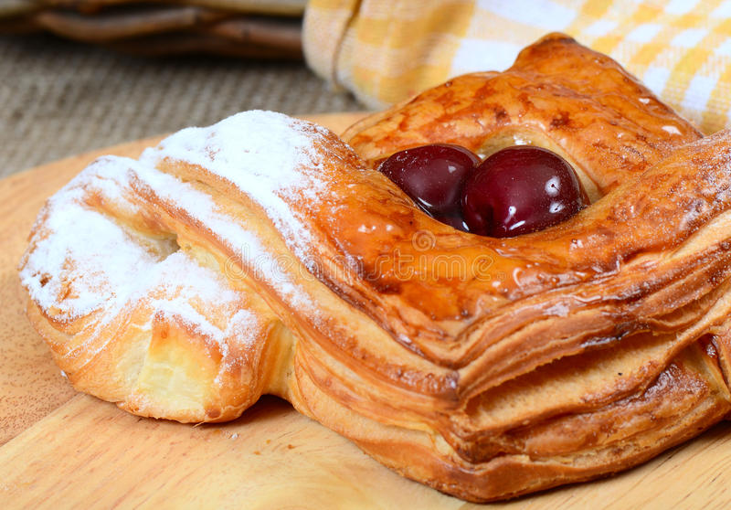 Roll from flaky pastry with cherry stock photo