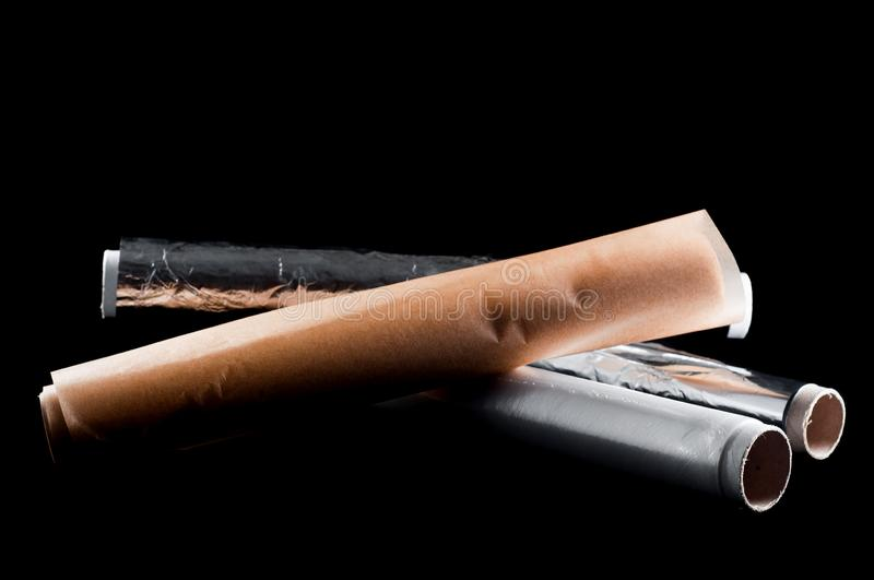 Roll of food parchment paper, food film and foil for the kitchen on a black background, isolate stock photo