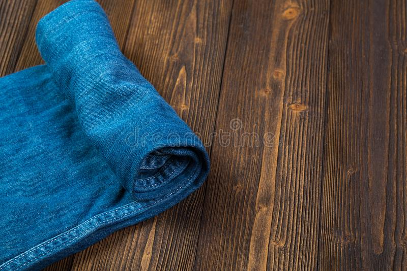Roll Frayed jeans or blue jeans denim collection on rough dark w stock photography