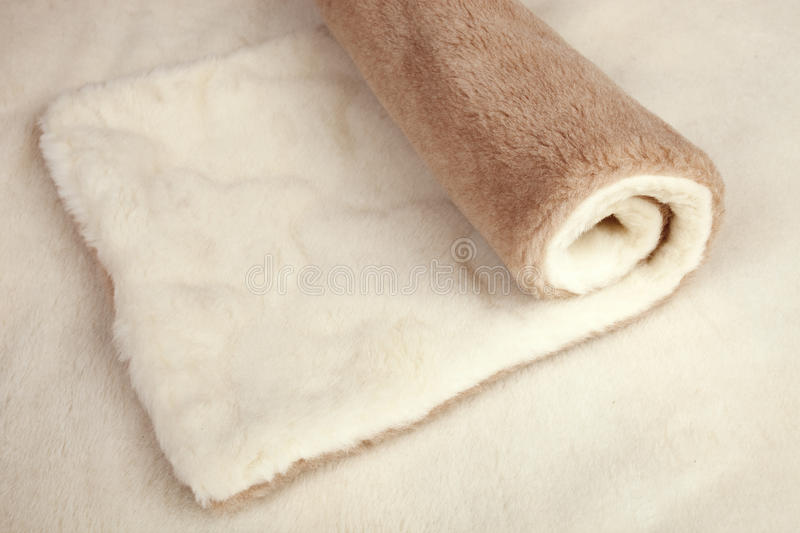 Roll of fur material. Roll of beige double-sided fur material stock image