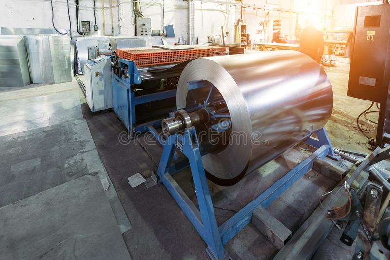Roll of galvanized steel sheet feeds steel sheets to the cutting machine for manufacturing metal pipes and tubes royalty free stock photography