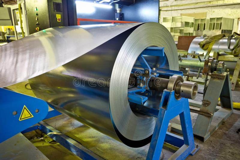 Roll of galvanized steel sheet for manufacturing metal pipes and tubes in the factory royalty free stock photos