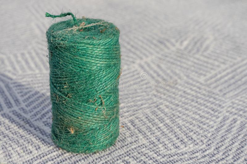 Roll of green small rope macro close up on patern striped blue and white carpet background. Decoration string roll stock image