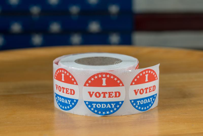 Roll of I Voted Today paper stickers on table with US Flag in background. Large roll of I Voted Today stickers ready for voters in the US elections with flag in stock photos