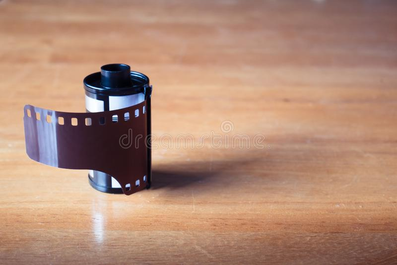 A roll of 35 mm film for cameras on wooden table.  stock images