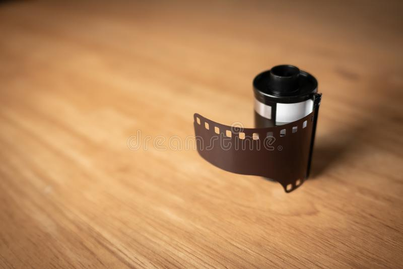 A roll of 35 mm film for cameras on wooden table.  royalty free stock photo