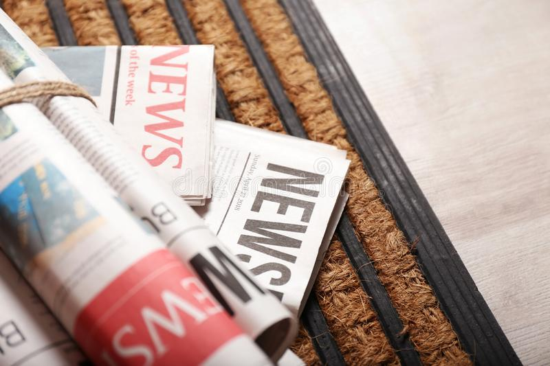 Roll of morning newspapers on entrance mat, closeup stock photo