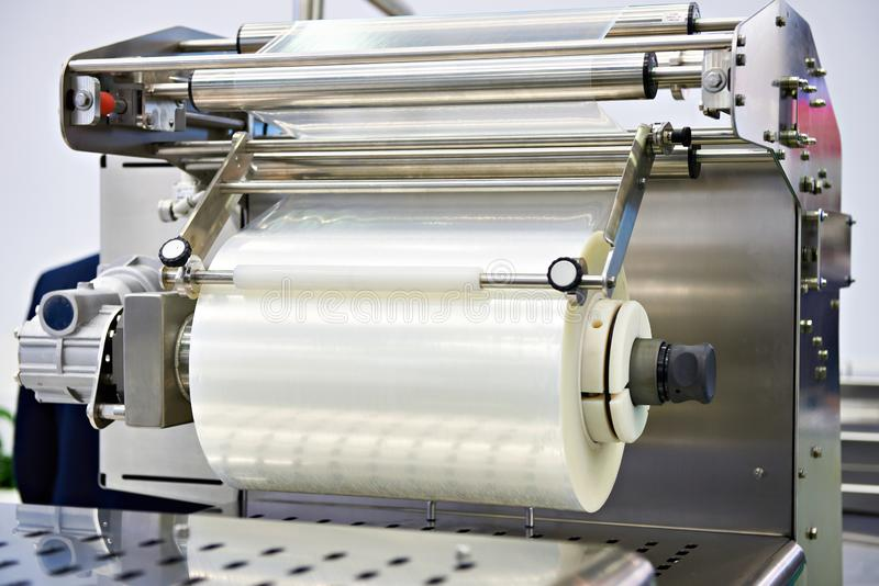 Roll of packaging film on machine food factory stock photos