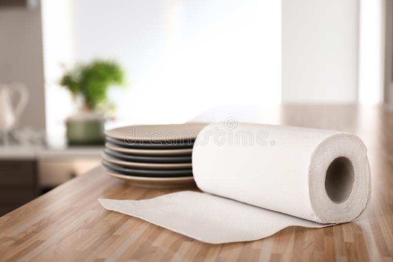 Roll of paper towels with plates on kitchen table royalty free stock image